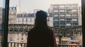 La cámara sigue la silueta feliz joven de la mujer que camina para abrir la ventana del balcón, disfruta de la cámara lenta de la metrajes