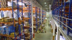 La cámara va entre los estantes en un almacén moderno con muchos estantes, estantes del almacén aéreo metrajes