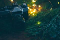 La cámara vieja en un fondo de madera con las ramas y las luces de árbol de navidad fotografía de archivo libre de regalías