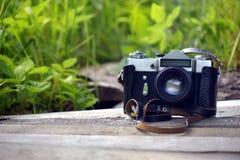 La cámara vieja se opone en un tablero de madera a un fondo de la hierba verde foto de archivo