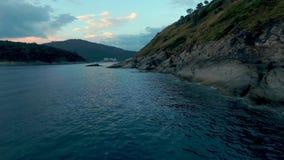 La cámara vuela alrededor de las rocas en el mar Foto de archivo