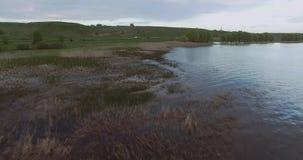 La cámara vuela en una baja altitud sobre la superficie del agua de un lago grande y se acerca gradualmente a la orilla metrajes
