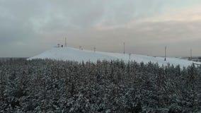La cámara vuela sobre el bosque hacia la estación de esquí Extremo del invierno de la visión aérea en casa de campo del esquí El  metrajes