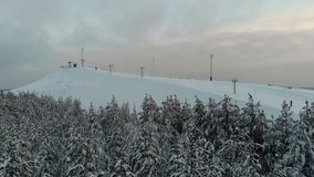 La cámara vuela sobre el bosque hacia la estación de esquí Extremo del invierno de la visión aérea en casa de campo del esquí El  almacen de video