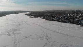 La cámara vuela sobre el río congelado con los pescadores en el invierno Silueta del hombre de negocios Cowering La cámara está v metrajes