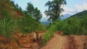 La cámara vuela sobre rastro de serpenteo entre el valle de la montaña