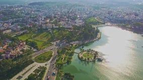 La cámara vuela y muestra el lago con la isla artificial y la ciudad
