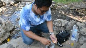 La cáscara tailandesa de la peladura del hombre hirvió el huevo después de cocinar la ebullición en aguas termales almacen de metraje de vídeo