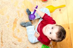 La céréale d'enfant a dispersé sur le plancher et jouer Images libres de droits
