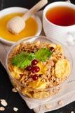 La céréale s'écaille avec les baies fraîches en bol, tasse de thé et miel Image libre de droits