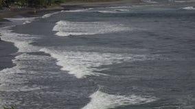 La côte de la mer tropicale dans le jour ensoleillé, vagues courues sur la côte avec les pierres noires, mouvement lent clips vidéos