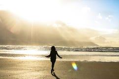 La côte lumineuse d'océan d'éclat de lumière du soleil de plage courante de fille ondule ciel chanceux heureux de l'eau le beau photos stock