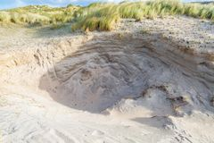 La côte néerlandaise de paysage dunaire avec des dérives de sable et le vent ont érodé les trous profonds Images stock