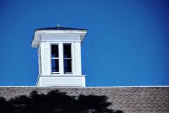 La cúpula blanca brillante se sienta encima del tejado del granero contra un cielo azul profundo Imagen de archivo