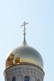 La cúpula y el cristiano de oro cruzan en iglesia contra el cielo Fotos de archivo libres de regalías