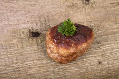 La côtelette avec le persil part sur la vieille table en bois Photo libre de droits