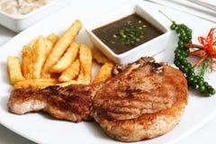 La côtelette de porc a servi avec les fritures et la sauce au poivre noire image stock