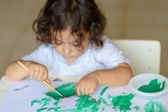 La caída adorable de la pintura del niño se va en la tabla foto de archivo