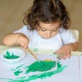 La caída adorable de la pintura del niño se va en la tabla imagen de archivo