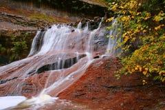 La caída deja la cascada roja Imagenes de archivo