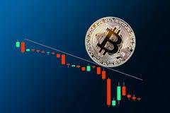 La caída del bitcoin de oro en fondo azul Fotografía de archivo