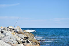 La caña de pescar en las rocas, ondas se estrella sobre las rocas Fotos de archivo libres de regalías