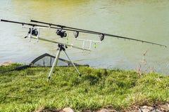 La caña de pescar se fija en la orilla del río Buena suerte para pescar imágenes de archivo libres de regalías