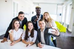 La cabeza de la compañía y de los funcionarios subordinados sonrientes que hacen el selfie en oficina Team Selfie imagenes de archivo