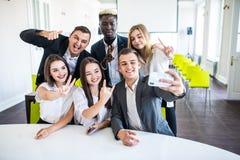 La cabeza de la compañía y de los funcionarios subordinados sonrientes que hacen el selfie en oficina Team Selfie fotografía de archivo libre de regalías