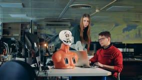 La cabeza del cyborg se está moviendo boca y la lengua bajo control de dos expertos almacen de metraje de vídeo
