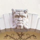 La cabeza del diablo talló sobre el arco de piedra de un chalet italiano Foto de archivo libre de regalías