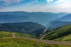 La cabina di funivia va giù dalla cresta verde Aibga Alte montagne nella foschia sull'orizzonte Krasnaya Polyana, Soci immagine stock