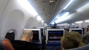 La cabina di passeggero con la gente dell'aeroplano durante il volo archivi video