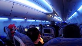 La cabina di passeggero con la gente dell'aeroplano durante il volo stock footage