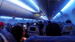 La cabina di passeggero con la gente dell'aeroplano durante il volo alla notte video d archivio