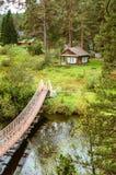 La cabina en el bosque en los bancos del río de Ural con puente colgante del río Irtysh, Rusia Fotos de archivo libres de regalías