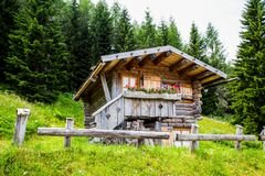 La cabina isolata della montagna nel legno/casa/ha isolato/verde/legno/montagna/dolomia/Italia immagini stock