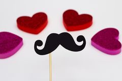 La cabine de photo étaye la moustache noire contre les coeurs brouillés sur le fond blanc Image libre de droits