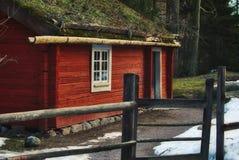 La cabine en bois de vieux cru étrange dans la forêt a peint rouge images libres de droits