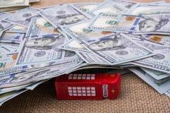 La cabine téléphonique modèle est couverte par les billets de banque de dollar US Photos libres de droits