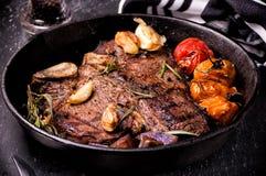 La cacerola asó a la parrilla el filete grande del t-hueso con ajo, tomates, las hierbas y el condimento Cierre para arriba Imagen de archivo