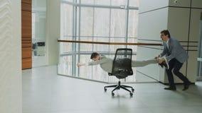 La cacerola de la cámara lenta tiró de dos hombres de negocios divertidos que montaban la silla de la oficina mientras que divirt