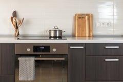 La cacerola está en una estufa de cerámica Cocina ligera con el horno, la tabla de cortar y otros elementos de los utensilios de  imagenes de archivo