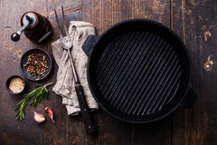 La cacerola, los condimentos y la carne vacíos de la parrilla del hierro negro bifurcan Imagen de archivo