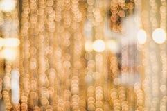 La cadena borrosa de oro de la Navidad enciende crear un bokeh hermoso Fotos de archivo libres de regalías