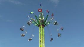 La cadena del cruce giratorio, atracción de la diversión, parque de atracciones con el cielo azul, cruce giratorio del carrusel,  metrajes