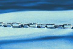 La cadena es metal Fondo suavemente azul Profundidad del campo baja Primer Foto de archivo libre de regalías