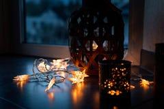 La cadena ligera y las velas crean una atmósfera acogedora rom?ntico Navidad fotografía de archivo libre de regalías