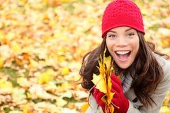 La caduta asiatica della tenuta della donna di autunno lascia in foresta Fotografia Stock