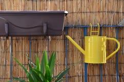 La caduta dell'annaffiatoio del metallo giallo sull'inferriata del balcone, bambù recinta il fondo Fotografia Stock